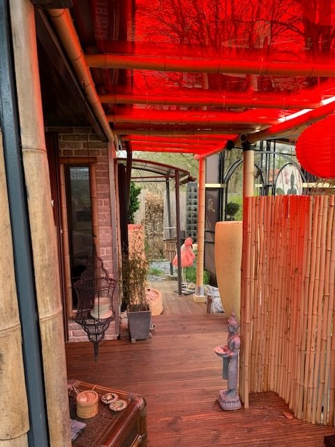 Door canopy made of red tinted plexiglass and bamboo